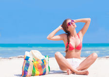 Young woman in bikini and sunglasses with beach Stock Photography