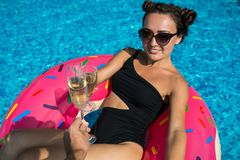 Young woman in bikini and sunglasses lies on colorful inflatable ring stock image