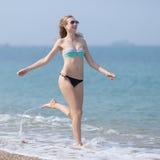 Young woman in bikini and sunglasses running along seashore Royalty Free Stock Photos