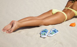 Young woman in bikini sunning on the beach. Unrecognizable beautiful young woman in bikini lying and sunning on the beach under the bright sun stock images