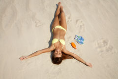 Young woman in bikini sunning on the beach Royalty Free Stock Images