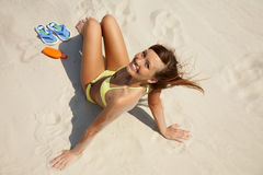Young woman in bikini sunning on the beach Stock Photography