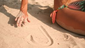 Young Woman in Bikini Swimsuit Drawing Heart on White Sand at Tropical Island Beach in Thailand. 4K, Slowmotion. Young Woman in Bikini Swimsuit Drawing Heart on stock video