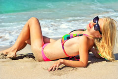 Young Woman in bikini swimwear sunbathing on the sandy Beach Seaside Royalty Free Stock Images