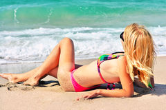 Young Woman in bikini swimwear sunbathing on the sandy Beach Seaside resort looking on Sea Stock Image