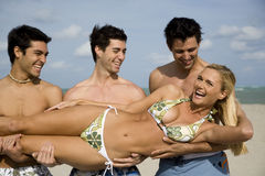 A young woman in a bikini with three male admirers Royalty Free Stock Photo