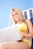 Young woman in bikini using laptop Stock Photo