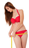 Young woman in bikini using measuring tape Royalty Free Stock Images