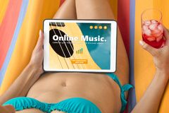 Young woman in a bikini visiting an online music website with he. R tablet device, lying on a hammock and having a drink Royalty Free Stock Image