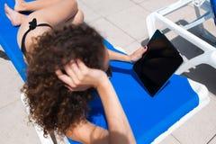 Young woman in bikini watching video on her digital tablet while sunbathe near pool Stock Photos