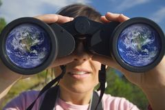 Young woman with binoculars. With the earth globe reflected in the lens Stock Images
