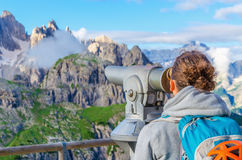 Young woman with binoculars in Dolomites, Italy. Young woman looking through binoculars at the wonderful view of the Dolomites Mountains, Dolomiti di Sesto or Royalty Free Stock Photography