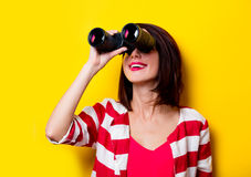 Young woman with binoculars. Portrait of the beautiful yound woman with binoculars on the yellow background Stock Images
