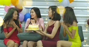 Young woman birthday girl is making wish, blowing candle on cake and clapping hands while her friends are congratulating stock footage