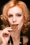 Young woman bite a cookie on black Stock Photography