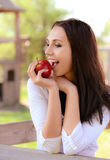 Young woman bites apple Royalty Free Stock Images