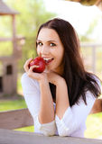 Young woman bites apple Royalty Free Stock Photos