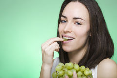 Young woman bites into grape Royalty Free Stock Image