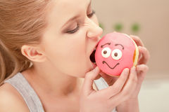 Young woman bites a pink donut Stock Photography