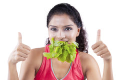 Young woman bites spinach leaves Stock Photo