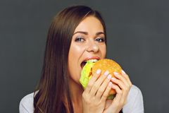 Young woman biting big burger isolated portrai. T on gray wall back Royalty Free Stock Image