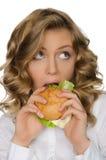 Young woman biting burger and looking away Stock Photos