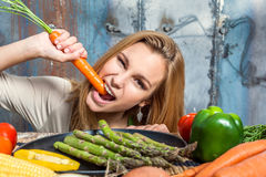 Young Woman Biting a Carrot Royalty Free Stock Photos