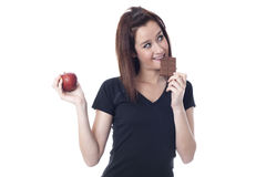 Young woman biting a chocolate bar and catching a fresh apple Stock Photos