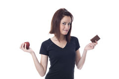 Young woman biting down on the lips torn between a chocolate bar and fresh apple Royalty Free Stock Images