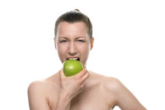 Young Woman Biting Fresh Green Apple Against White Stock Photo