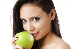 Young woman biting a green apple Stock Photo