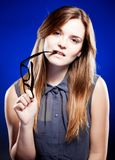 Young woman biting a nerd glasses with interested look Stock Images