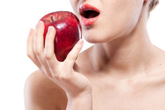 Young woman biting red apple on white Stock Photo