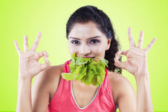 Young woman biting spinach with OK sign Royalty Free Stock Photos