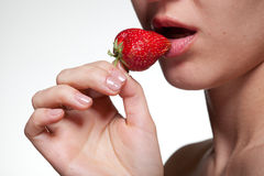 Young woman biting strawberry isolated on white Royalty Free Stock Image