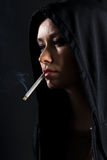 Young woman on a black background smoking a cigarette Stock Photography