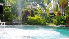 Young woman in black bikini jumping into swimming pool in lush palm tree jungle on tropical island. Girl enjoying summer. Vacation. slow motion. 1920x1080, hd stock video