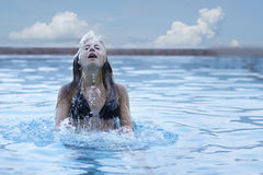 Young woman with black bikini jumping up from under water. Royalty Free Stock Image
