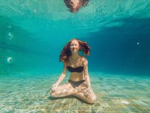 Young woman in black bikini in yoga position underwater in diving aquarium, full body shot, front view.  stock photos