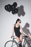 Young woman in black bodysuit and sunglasses posing with bicycle and balloons in studio Stock Image