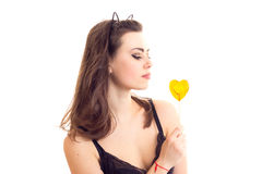 Young woman in black bra with candy. Attractive young woman with long brown hair and cat ears on her head wearing in black lace bra holding heart-shaped candy on Stock Images