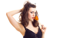 Young woman in black bra with candy. Young beautiful woman with long brown hair and cat ears on her head wearing in black lace bra eating heart-shaped candy on Royalty Free Stock Photo