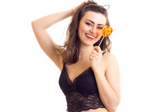 Young woman in black bra with candy. Laughing young woman with long brown hair and cat ears on her head wearing in black lace bra holding heart-shaped candy on Royalty Free Stock Photos