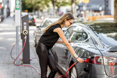 Woman charging electric car outdoors. Young woman in black clothes putting connector into the electric car outdoors on the street in Rotterdam city Stock Image