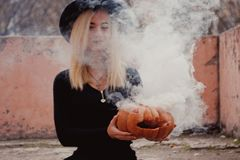 Young woman in the black coat holding the halloween pumpkin with the white smoke coming from inside of it in the autumn. Young woman in the black clothing royalty free stock photos