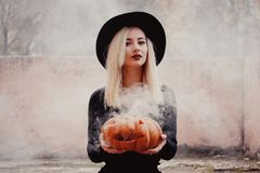 Young woman in the black coat holding the halloween pumpkin with the white smoke coming from inside of it in the autumn. Young woman in the black clothing stock photo