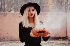 Young woman in the black coat holding the halloween pumpkin with the white smoke coming from inside of it in the autumn royalty free stock photography