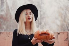 Young woman in the black coat holding the halloween pumpkin with the white smoke coming from inside of it in the autumn stock photos