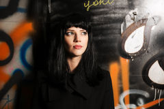 Young fashion woman in black coat at the graffiti wall Royalty Free Stock Photos