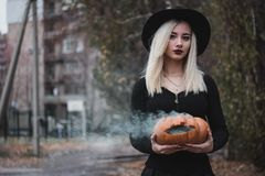 Young woman in the black coat holding the halloween pumpkin with the white smoke coming from inside of it in the autumn. Young woman in the black clothing royalty free stock image